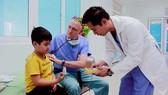 Bác sĩ James Nguyen và bác sĩ David Paul Norton (giữa) khám bệnh cho bé Ân tại Bệnh viện Sản nhi Quảng Ngãi