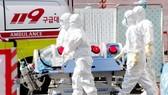 Nhân viên y tế chuyển bệnh nhân nhiễm Covid-19 tới bệnh viện ở Daegu, Hàn Quốc ngày 4-3