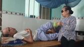 Cụ bà Nguyễn Thị Huê bị mù phải gắng mò mẫm đút từng thìa cháo cho chồng là cụ ông Nguyễn Văn Nữ