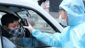 Tổ phòng dịch Covid-19 đo thân nhiệt người tham gia giao thông ở cầu Đồng Nai, cửa ngõ vào TPHCM. Ảnh: PHẠM MINH