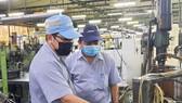 Anh Lê Chí Chung (trái, Công ty Juki) cùng đồng nghiêp tìm hiểu hoạt động của máy để đưa ra sáng kiến cải tiến. Ảnh: THÁI PHƯƠNG