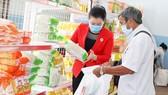 Tình nguyện viên giúp người khó khăn chọn nhu yếu phẩm tại phiên chợ nhân đạo tổ chức ở huyện Nhà Bè