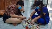 Hai chị em Phan Ngọc Phương Trinh và Phan Ngọc Phương Vy đập heo đất để lấy tiền ủng hộ quỹ