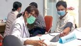Nhân viên y tế đo huyết áp cho người dân trước khi tiêm vaccine phòng Covid-19