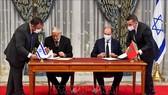 Các đại diện của Morocco và Israel ký thỏa thuận thiết lập quan hệ ngoại giao tại Rabat, Morocco ngày 22-12. Ảnh: AFP/TTXVN