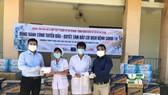Giám đốc Trung tâm Báo chí và hợp tác truyền thông quốc tế tại TPHCM Lê Tự Phương Quang (trái) cùng mạnh thường quân trao quà hỗ trợ đội ngũ y, bác sĩ, các nhân viên y tế