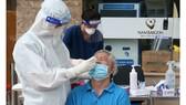 Nhân viên y tế Bệnh viện Đa khoa Quốc tế Nam Sài Gòn lấy mẫu  xét nghiệm cho người dân.  Ảnh: HOÀNG HÙNG