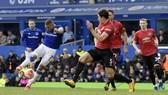 Richarlison sút bóng trước Harry Maguire (Man United)