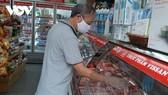 Khách hàng đang lựa chọn thịt lợn tại cửa hàng.