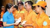 Đại diện Liên đoàn Lao động quận 1 tặng quà công nhân vệ sinh vào đêm 30 Tết Canh Tý 2020. Ảnh: HỒNG HẢI