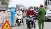 Lực lượng trực chốt kiểm soát cấp tỉnh tại ngã ba Hoàng Long, cửa ngõ phía tây thành phố Hải Dương kiểm tra kỹ giấy tờ của người dân lưu thông qua đây. (Ảnh: Mạnh Minh/TTXVN)
