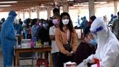 Người lao động tại Công ty Pousung Việt Nam làm các thủ tục trước khi vào nhà máy làm việc. (Ảnh: Công Phong/TTXVN)