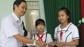 Ông Trần Văn Phong, Trưởng Văn phòng đại diện báo SGGP khu vực Đông Nam bộ tặng học bổng cho học sinh