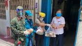 Bộ đội cùng cán bộ phường xã đưa nhu yếu phẩm đến tận nhà dân