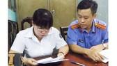 Nguyên chấp hành viên Đinh Thị Anh Đào (trái) lúc bị bắt