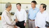 Chủ tịch UBND TPHCM Nguyễn Thành Phong ân cần thăm hỏi đồng chí Trần Tài Ba. Ảnh: KIỀU PHONG