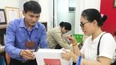 Công chức phường Bến Thành, quận 1, TPHCM đang tiếp nhận, chứng thực hồ sơ sao y của người dân ngoài giờ hành chính. Ảnh: KIỀU PHONG