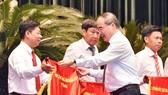 Đồng chí Nguyễn Thiện Nhân, Bí thư Thành ủy TPHCM, trao cờ thi đua chính phủ cho các tập thể.  Ảnh: VIỆT DŨNG