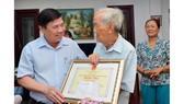 Đồng chí Nguyễn Thành Phong, Chủ tịch UBND TPHCM chúc thọ cụ Lê Duyên. Ảnh: VIỆT DŨNG