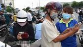 Người dân thực hiện khai báo y tế điện tử trên điện thoại khi ra, vào quận Gò Vấp. Ảnh: ĐÌNH LÝ