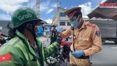 Lực lượng chức năng TPHCM kiểm tra một shipper trong ngày 26-7. Ảnh: VĂN MINH