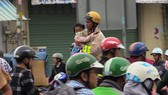 Hình ảnh CSGT TPHCM bồng bé gái qua vũng ngập. Ảnh: CHÍ THẠCH