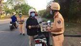 Lực lượng CSGT TPHCM phát tờ rơi tuyên truyền an toàn giao thông, phòng chống dịch Covid-19 nhằm nâng cao nhận thức của người dân. Ảnh: CA cung cấp