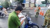 Công an hướng dẫn người dân khai báo tại chốt trạm kiểm soát ở TPHCM sáng ngày 29-8. Ảnh: CHÍ THẠCH