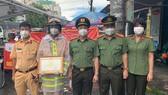 Đại tá Hoàng Văn Hà, Phó Cục trưởng Cục An ninh điều tra Bộ Công an (A09) trao tặng bằng khen cho Thiếu tá Lê Hoàng tại chốt kiểm soát phòng chống dịch. Ảnh: CHÍ THẠCH