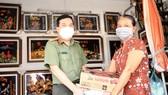 Đại tá Nguyễn Sỹ Quang, Phó Giám đốc Công an TPHCM trao quà cho gia đình chị Thuỷ. Ảnh: DŨNG PHƯƠNG