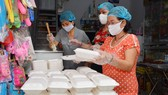 Một gia đình ở quận Phú Nhuận, TPHCM nấu cơm phát từ thiện cho người nghèo và ở bệnh viện, sáng 7-4-2020. Ảnh: VIỆT DŨNG