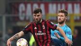 Patrick Cutrone (trái, AC Milan) tranh bóng với Shkodran Mustafi (Arsenal)