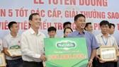 HLV Châu Đức Thành thay mặt toàn đội nhận phần thưởng từ ông Lê Nguyên Hòa