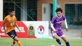 Hải Yến nỗ lực đi bóng trước sự bám sát của cầu thủ U15 Thái Sơn Bắc