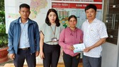 Ông Nguyễn Hữu Quế (bên phải), Chủ tịch UBND TP Pleiku  phối hợp với đại diện Báo SGGP (bên trái) cùng UBND phường Trà Bá (thứ 2 từ trái qua) trao tiền hỗ trợ của bạn đọc Báo SGGP cho gia đình em Liên