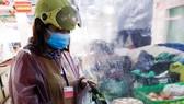 Thành viên tổ đi chợ thuộc ban điều hành tổ dân phố 43, phường An Hải Bắc, quận Sơn Trà mặc áo mưa đi chợ truyền thống