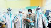 Chị M. lưu giữ tấm hình kỷ niệm với đội ngũ bác sĩ cứu sống chị cùng con trai. Ảnh: Bệnh viện dã chiến Hòa Vang