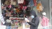 Phụ huynh ghi danh sách đồ dùng học tập cần mua cho học sinh gửi vào trong quầy bán hàng để tránh tiếp tục trực tiếp