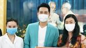 Đại diện UBMTTQ VN tại TPHCM nhận bảng tượng trưng ủng hộ của ca sĩ Nguyễn Phi Hùng và Vy Oanh