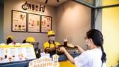 Khách mua thực phẩm tiêu dùng nhanh tại một cửa hàng có giao hàng trực tuyến