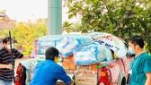 Thành viên Câu lạc bộ Xe bán tải Đà Nẵng đưa hàng hóa, nhu yếu phẩm,  đồ bảo hộ chống dịch đến các khu cách ly. Ảnh: NGUYỄN CƯỜNG