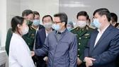Phó Thủ tướng Vũ Đức Đam và Bộ trưởng Bộ Y tế Nguyễn Thanh Long động viên một tình nguyện viên được tiêm thử nghiệm vaccine ngừa Covid-19 của Việt Nam