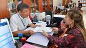 Công chức tận tình, chu đáo với người dân làm thủ tục hành chính tại UBND quận 4, TPHCM. Ảnh: VIỆT DŨNG