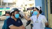 Người bệnh vào Bệnh viện Da liễu TPHCM phải bắt buộc đeo khẩu trang và được kiểm tra thân nhiệt, khai báo y tế ngay từ cổng. Ảnh: MINH NAM