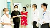 Trưởng Ban Dân vận Thành ủy TPHCM Nguyễn Hữu Hiệp (thứ 2 từ phải qua) thăm, động viên và trao quà hỗ trợ đến các hộ dân vừa tạm chuyển chỗ ở tới Nhà nghỉ Công đoàn Thanh Đa, quận Bình Thạnh