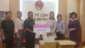 Đại diện Công ty Mỹ phẩm thương hiệu Việt M.O.I Cosmetics trao bảng tượng trưng số tiền tặng Bộ đội biên phòng