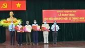 Đồng chí Trần Lưu Quang (bìa trái) tặng hoa chúc mừng các đảng viên 60 năm, 55 tuổi Đảng