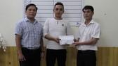 Đại diện Báo SGGP tại miền Trung và chính quyền địa phương trao tiền hỗ trợ cho gia đình cháu Huy
