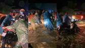 CSGT và các tình nguyện giúp người dân đẩy xe qua dòng nước xiết. Ảnh: Chụp màng hình clip trên mạng xã hội