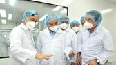 Chủ tịch nước Nguyễn Xuân Phúc và Bí thư Thành ủy TPHCM Nguyễn Văn Nên nghe giới thiệu về vaccine Nano Covax. Ảnh: VIỆT DŨNG
